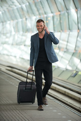 Young Caucasian Man Walking in City with Cell and Suitcase