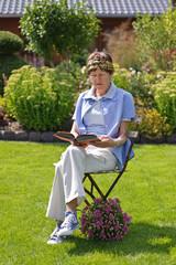 Frau ließt Buch im Garten