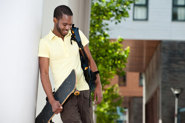 Young Black Male With Skateboard and Bag