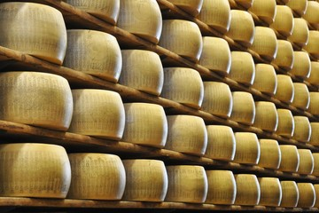 Storing of Parmesan cheese on wooden shelves