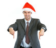 Smiling businessman in Santa's hat pointing down
