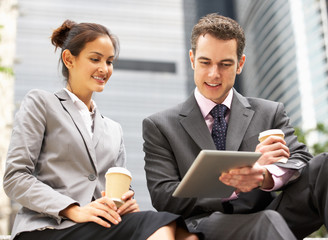 Businessman And Businesswoman Using Digital Tablet Outside Offic