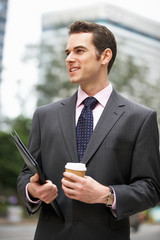 Businessman Walking Along Street Holding Takeaway Coffee