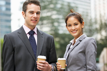 Businessman And Businesswoman Chatting In Street Holding Coffee