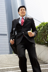 Chinese Businessman Rushing Down Steps Carrying Bag And Coffee
