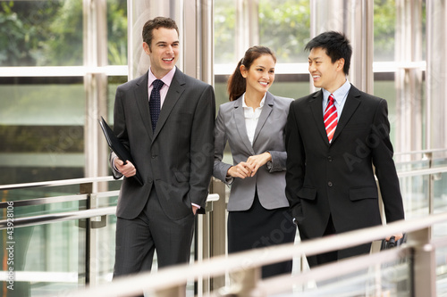 Three Business Colleagues Having Discussion Whilst Walking Outsi