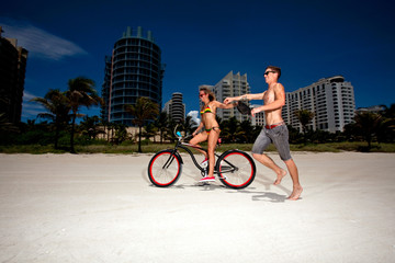 Young couple on Miami Beach Riding bikes and having fun