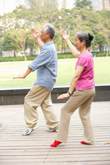 Senior Chinese Couple Doing Tai Chi In Park