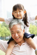 Chinese Grandfather Giving Granddaughter Ride On Shoulders