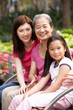 Female Multi Genenration Chinese Family Group Sitting On Bench