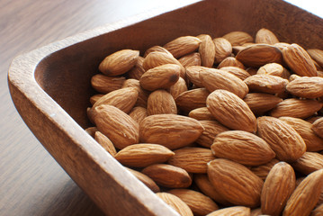 Almonds nuts in wooden bowl
