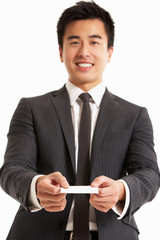 Studio Portrait Of Chinese Businessman Offering Business Card