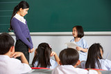 Pupil And Teacher Standing By Blackboard In Chinese School