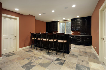 Bar in basement with dark wood cabinetry