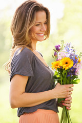 Woman Walking Through Summer Field Carrying Bouquet Of Flowers