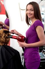 Junge Frau föhnt Kundin die Haare