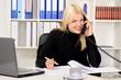 Auszubildende telefoniert am Schreibtisch