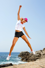 Attractive woman with winning attitude jumping.