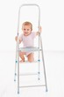 Adorable baby girl climbing on ladder smiling