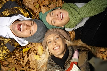 Young friends among autumn leaves smiling