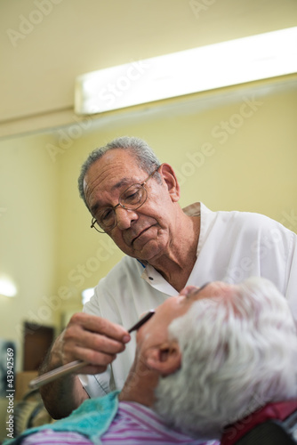 Elderly barber with razor shaving client in barber shop