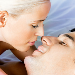 Young kissing cheerful attractive couple