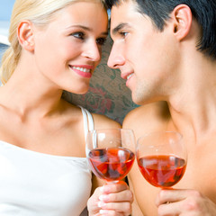 Cheerful couple with glasses of redwine