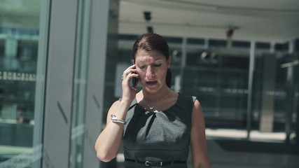 Businesswoman walking and talking on cellphone, steadicam shot