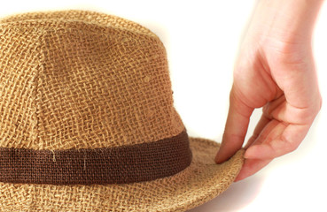 Woman's hand with summer straw hat on white background