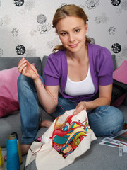 The beautiful girl in apartment embroiders a colourful picture