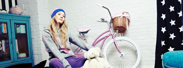 young woman with pink bike at home