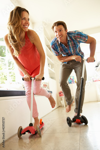Couple Riding Childrens Scooters Indoors