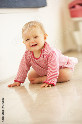 Unhappy Baby Girl Sitting On Floor Crying