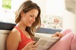 Woman Relaxing With Newspaper At Home