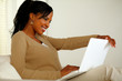 Lovely black woman smiling and looking to laptop