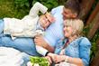 Смеющийся мальчик с родителями на траве у забора в летнем саду