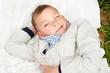 Красивый улыбающийся мальчик лежит на белом пледе и подмигивает
