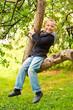 Счастливый мальчик сидит на ветке дерева и смеётся