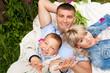 Счастливые родители с сыном лежат рядом на траве