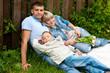 Любящие родители с сыном сидят на траве у забора в летнем саду
