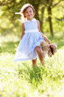 Young Girl Walking Through Summer Field Carrying Teddy Bear