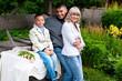 Красивая семья с сыном сидят на колодце в саду летом