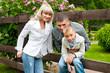 Счастливая семья с сыном в живописном парке летом у забора