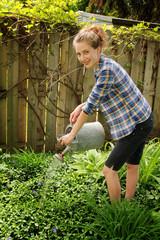 Teen watering flowers
