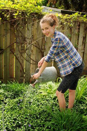 Teen watering flowers