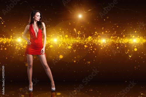 brünette Frau in rotem Minikleid vor Lichterhintergrund