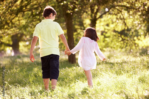 Boy And Girl Walking Through Summer Field Together