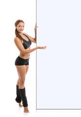 Fitness woman presenting empty billboard