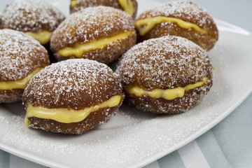 Berliners with cream on a white plate