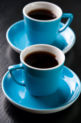 Vertical shot of two turquoise espresso cups on a black table